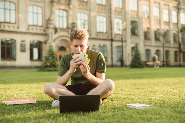 Knappe universiteitsstudent die smakelijke sandwich eet