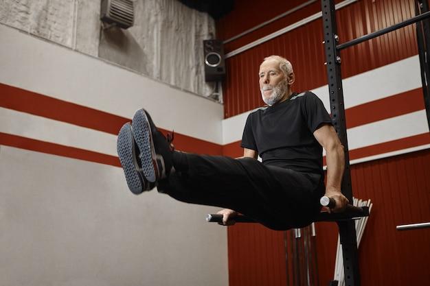 Knappe usnhaven gepensioneerde man in stijlvolle sportkleding crossfit training in de sportschool doen, benen verhogen tijdens het trainen op de pull-up bar, buikspieren versterken. fitness-, sport- en pensioenconcept