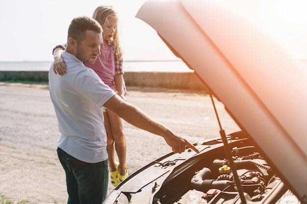 Knappe vader die zijn dochter van de schoolleeftijd onderwijst om motorolie te veranderen of familieauto te herstellen.