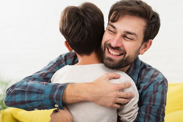 Knappe vader die zijn zoon omhelst