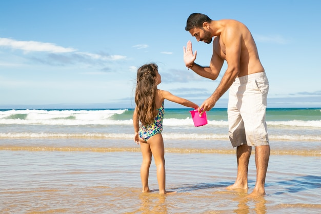 Knappe vader en dochtertje die samen schelpen met emmer op strand plukken, high five geven