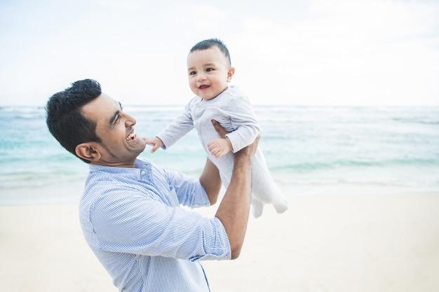 Knappe vader spelen met zijn schattige zoon op het strand
