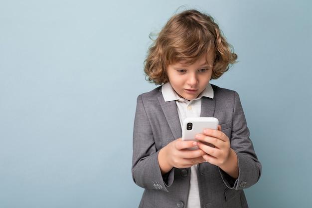 Knappe verbaasde jongen met krullend haar grijs pak dragen en houden geïsoleerd met behulp van telefoon