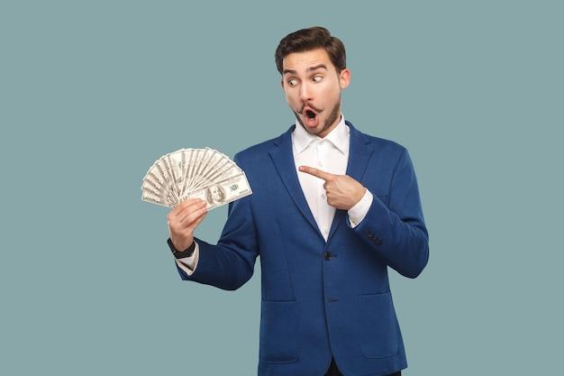 Knappe verbaasde zakenman in blauwe jas die staat en veel dollars in de hand houdt, wijzend en kijkend naar geld met een verbaasd verrast gezicht. binnen, studio-opname geïsoleerd op lichtblauwe achtergrond.