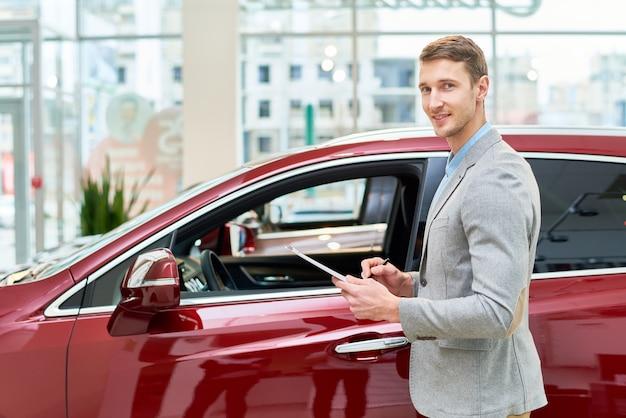 Knappe verkoopassistent presenteren van auto's