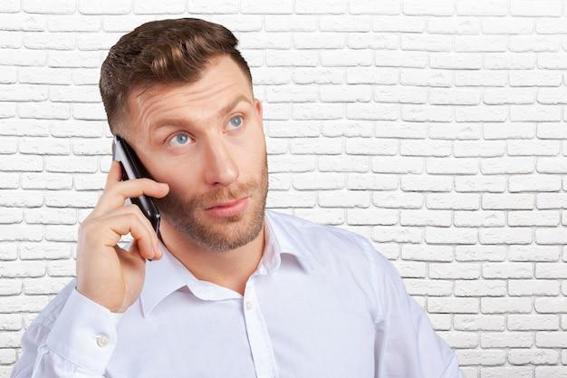 Knappe verkoper die op mobiele telefoon spreekt