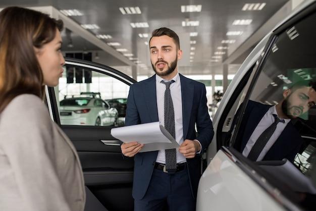 Knappe verkoper selling cars in showroom