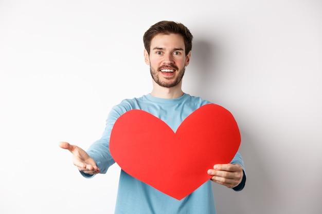 Knappe verliefde man die een bekentenis aan je aflegt, hand naar de camera wijst, een groot rood hartuitsparing vasthoudt op valentijnsdag, romantische serenade zingt, staande op een witte achtergrond.