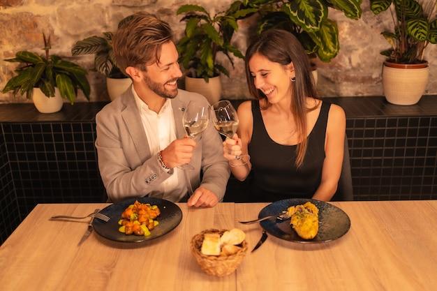 Knappe verliefde paar in een restaurant, toast op de glazen wijn, valentijnsdag vieren, overhead schot