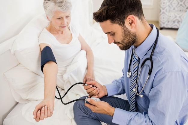 Knappe verpleegster die bloeddruk van bejaarde thuis controleert
