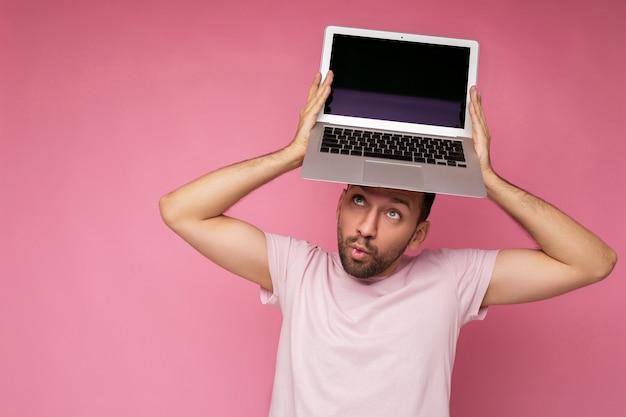 Knappe verrast brunet man met laptopcomputer kijken camera in t-shirt op geïsoleerde roze achtergrond.