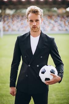 Knappe voetballer bij stadion in pak