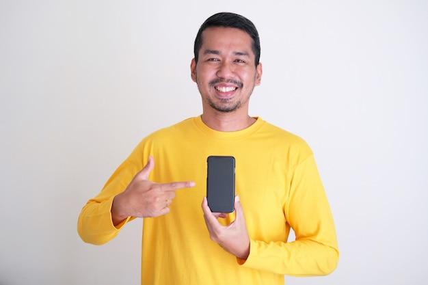Knappe volwassen aziatische man die zelfverzekerd glimlacht terwijl hij met de vinger op het lege scherm van de gsm wijst