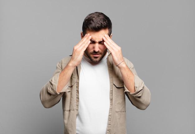 Knappe volwassen blonde man die gestrest en gefrustreerd kijkt, onder druk werkt met hoofdpijn en last heeft van problemen