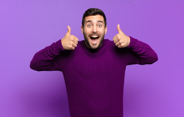 Knappe volwassen blonde man die lacht en er in het algemeen gelukkig, positief, zelfverzekerd en succesvol uitziet, met beide duimen omhoog