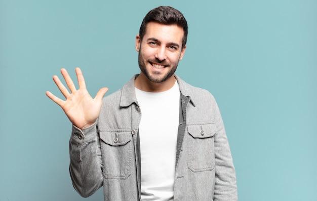 Knappe volwassen blonde man die lacht en er vriendelijk uitziet, nummer vijf of vijfde toont met de hand naar voren, aftellend