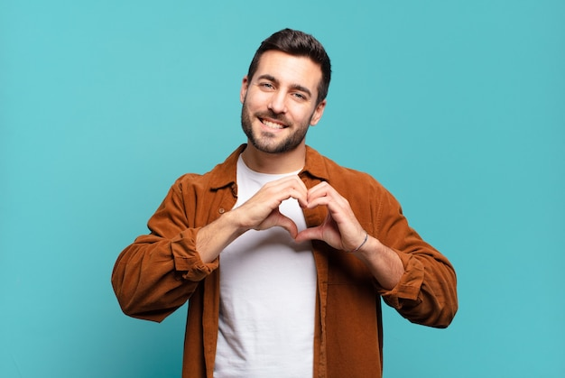 Knappe volwassen blonde man die lacht en zich gelukkig, schattig, romantisch en verliefd voelt, hartvorm maakt met beide handen