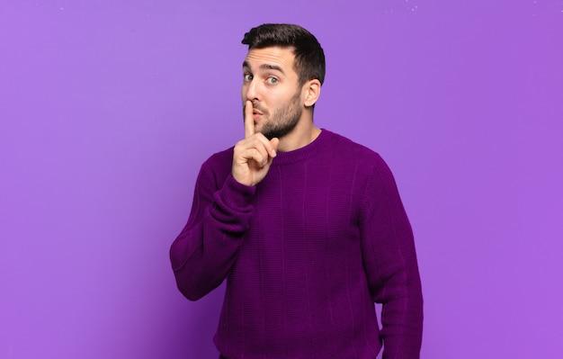 Knappe volwassen blonde man die om stilte en stilte vraagt, met de vinger voor de mond gebaart, shh zegt of een geheim bewaart