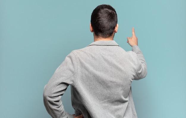 Knappe volwassen blonde man die staat en wijst naar object op kopieerruimte, achteraanzicht
