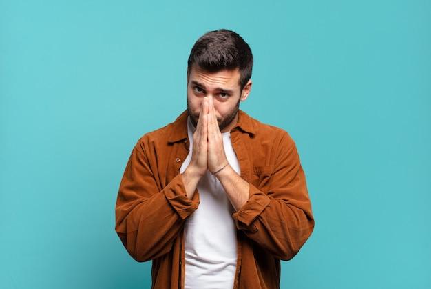 Knappe volwassen blonde man die zich bezorgd, hoopvol en religieus voelt, trouw bidt met ingedrukte handpalmen, smekend om vergiffenis
