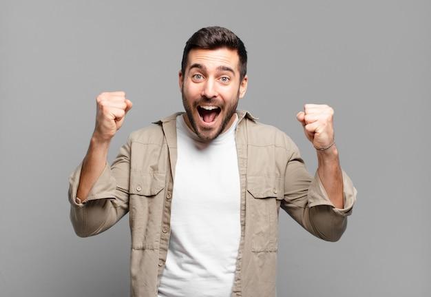 Knappe volwassen blonde man die zich blij, verrast en trots voelt, schreeuwt en succes viert met een grote glimlach