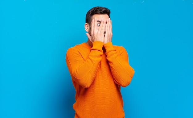 Knappe volwassen blonde man die zijn gezicht bedekt met handen, tussen de vingers gluurt met een verbaasde uitdrukking en opzij kijkt