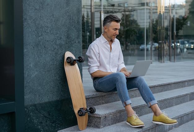 Knappe volwassen freelancer met behulp van laptop, typen op toetsenbord, buiten zitten