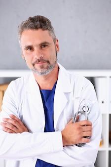 Knappe volwassen glimlachende mannelijke arts met gekruiste armen op de borst
