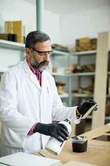 Knappe volwassen ingenieur in het laboratorium onderzoekt keramische tegels
