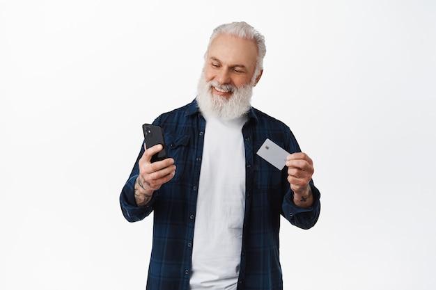 Knappe volwassen man betalen met creditcard op smartphone, kaart tonen en kijken naar telefoon met lachend gezicht, online winkelen, staande tegen witte muur
