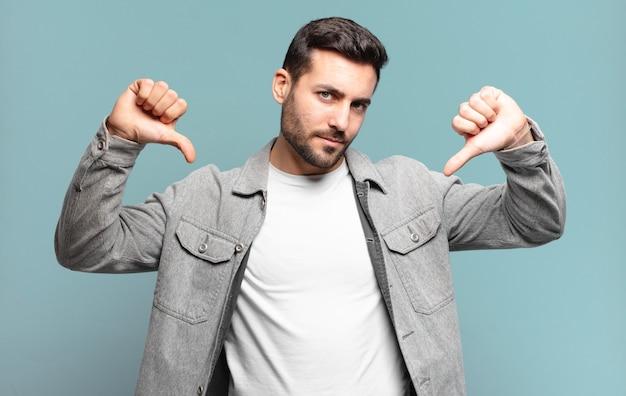 Knappe volwassen man die verdrietig, teleurgesteld of boos kijkt, duimen naar beneden laat zien in onenigheid, zich gefrustreerd voelt
