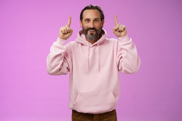 Knappe volwassen man grijs haar baard dragen stijlvolle hipster losse hoodie wijzende wijsvingers...