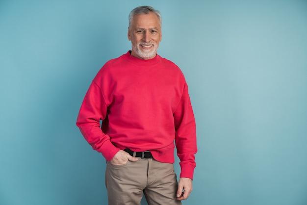 Knappe, volwassen man in een karmozijnrode trui poseren