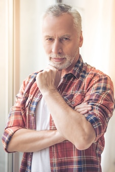 Knappe volwassen man in vrijetijdskleding wrijft over zijn kin