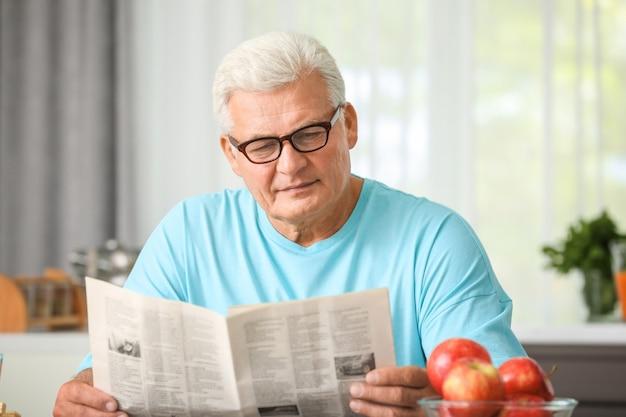 Knappe volwassen man krant lezen in de keuken
