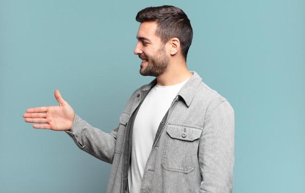 Knappe volwassen man lacht, groet je en biedt een handdruk om een succesvolle deal, samenwerkingsconcept te sluiten