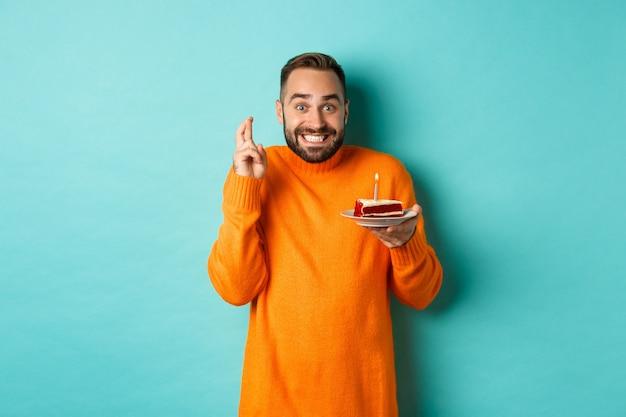 Knappe volwassen man viert verjaardag, kaars op taart uitblazen en wens doen, staande tegen turquoise muur
