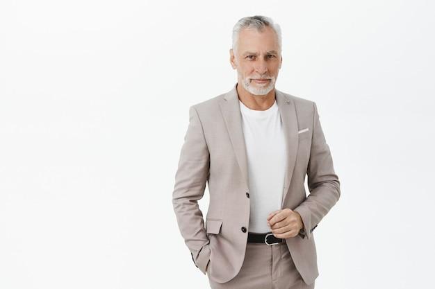 Knappe volwassen zakenman die zelfverzekerd en glimlachend kijkt
