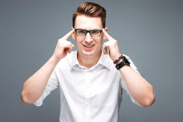 Knappe volwassen zakenman in dure horloge, zwarte bril en wit overhemd