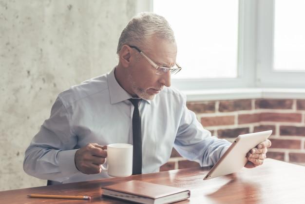 Knappe volwassen zakenman in formele pak en glazen