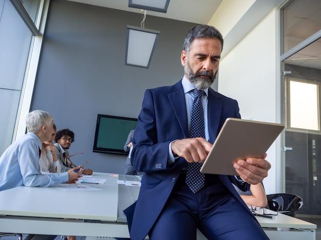 Knappe volwassen zakenman, leider die op kantoor werkt