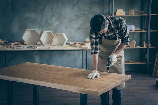 Knappe voorzichtige man montage handgemaakte plaat tafel afwerking acties voor verkoop website eigen houten bedrijf industrie houtwerk winkel garage binnenshuis