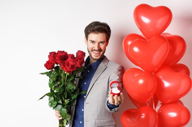 Knappe vriend in pak die een huwelijksaanzoek doet, verlovingsring toont en zeg met me trouwen, rode rozen vasthouden, staande in de buurt van valentijnsdag ballonnen, witte achtergrond.