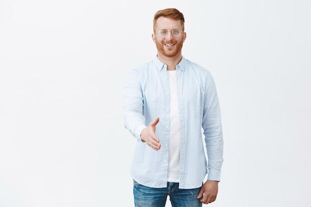 Knappe, vriendelijke en charmante roodharige man met borstelharen in bril en shirt, handen naar in handdrukgebaar trekken en gelukkig glimlachen