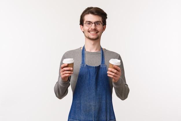 Knappe vriendelijke glimlachende jonge kaukasische mannelijke werknemer, coffeeshopeigenaar in schort maakte een bestelling voor afhaalmaaltijden, hield twee kopjes drank vast, gaf de klant hun drankje,