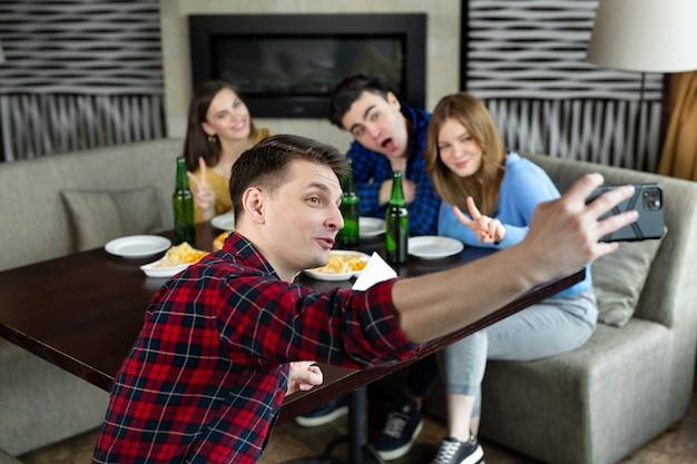 Knappe vrienden selfie maken en glimlachen tijdens het rusten in de pub