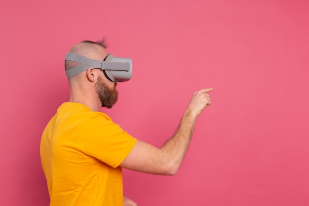 Knappe vrijetijdskleding mannen in vr-bril zijaanzicht wijzend naar de linker tekstruimte