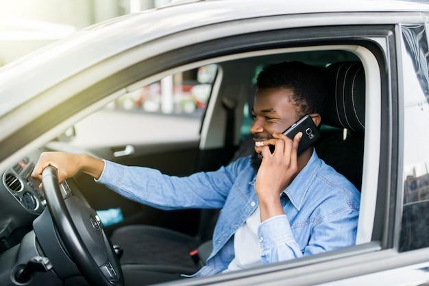 Knappe vrolijke afrikaanse man praten over zijn slimme telefoon