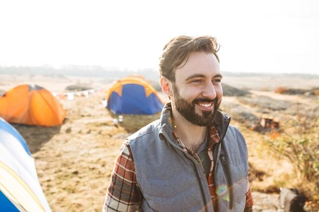 Knappe vrolijke bebaarde man die buiten kampeert