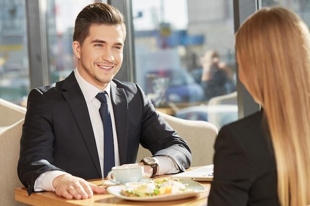 Knappe vrolijke bedrijfsmens die aan zijn vrouwelijke collega tijdens ontbijt bij koffiewinkel spreekt